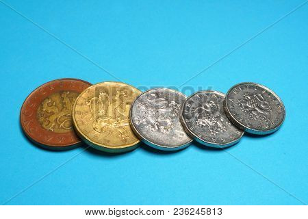 Czech crowns, metal money. Czech gold coins on a blue background. Detail of spent coins. Savings in small money.