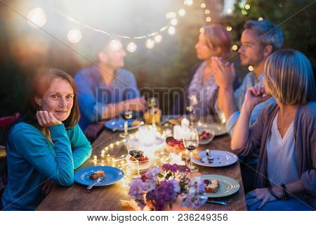 Group Of Friends Gathered Around A Table In A Garden On A Summer Evening To Share A Meal And Have A