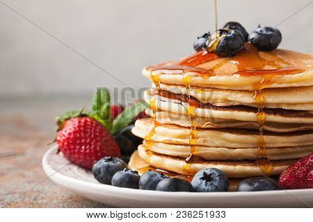 Close-up Delicious Pancakes, With Fresh Blueberries, Strawberries And Maple Syrup On A Light Backgro