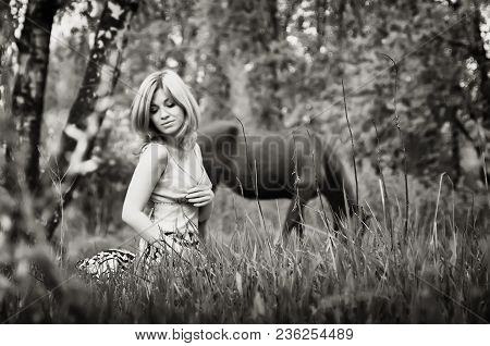 Young Beautiful Blond Woman With Long Hair Sitting In The Grass Against A Grazing Horse On The Fores