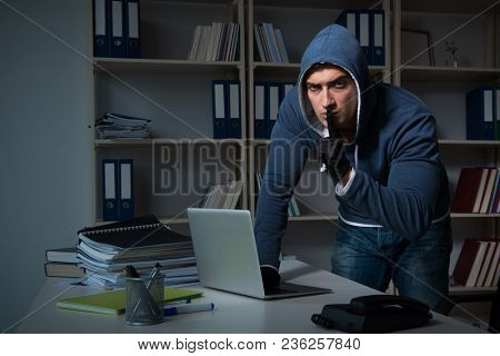 Young hacker hacking into computer at night