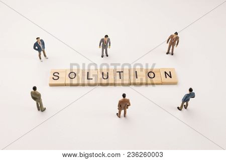 Miniature Figures Businessman : Meeting On Solution Word By Wooden Block Word On White Paper Backgro