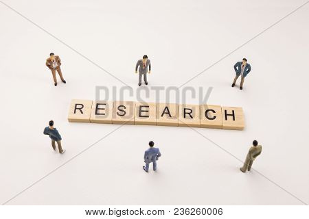 Miniature Figures Businessman : Meeting On Research Word By Wooden Block Word On White Paper Backgro