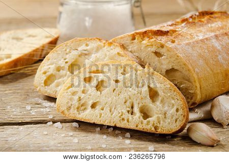 Ciabatta Bread. Slices Of Ciabatta With Garlic, Salt On A Wooden Table On Linen Cloth. Rustic Style,