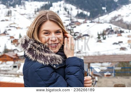 Young Female Tourist Smiling At The Camera In Grindelwald, Swiss Alps On Wintertime
