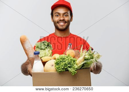 Delivery Concept - Handsome African American Delivery Man Carrying Package Box Of Grocery Food And D