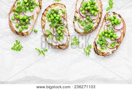 Cream Cheese, Green Peas, Radishes And Micro Greens Spring Sandwiches On A Light Background, Top Vie