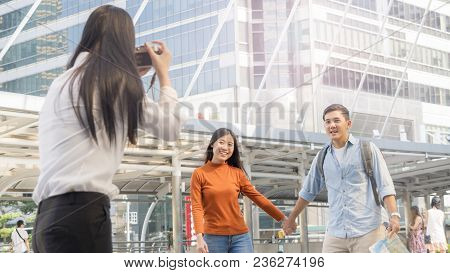 Business Woman Hold Camera To Shoot The Traveler Couple People At Urban City And Modern Building. Ho
