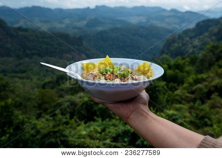 Tom Yum Noodle In Hand With Mountain View In Behind, Thai Signature Food With Natural