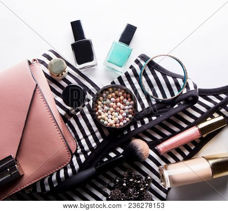 Stylized feminine flatlay with glasses, foundation, lip gloss, powder, brush, handbag, striped shirt isolated on white top view.