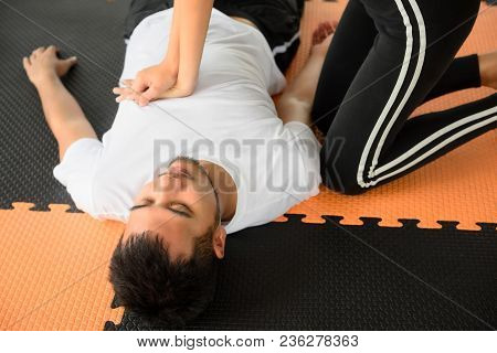Fitness trainer woman giving cardiopulmonary resuscitation or CPR (life saving techniques) to heart attack drowning or heat stroke man in sport club. Urgent accident for Healthcare safety concept. poster