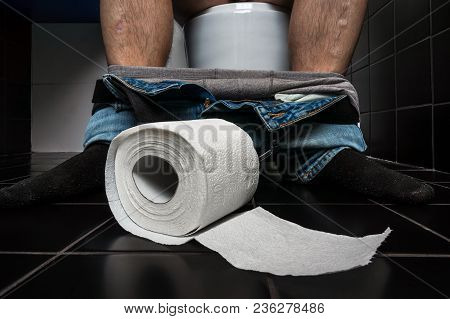 Man Suffers From Diarrhea Is Sitting On Toilet Bowl