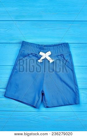 Baby Boy Blue Organic Shorts. Baby Blue Shorts On Blue Wooden Background, Vertical Image. Baby Boy S