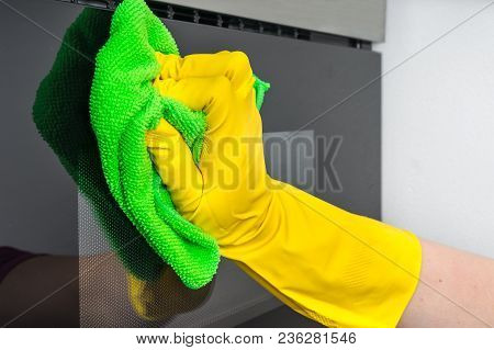 Hand In Glove With Green Rag Wiping Microwave Oven - Housework And Housekeeping Concept