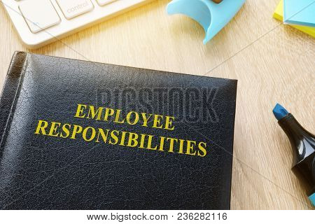 Book About Employee Responsibilities On An Office Table.
