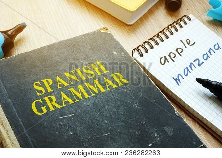 Learn Spanish Grammar Concept. Book And Notebook On A Desk.