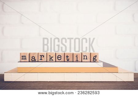 The Word Marketing, Text On Wooden Cubes On Top  Books. Background Copy Space, Vintage Minimal Style