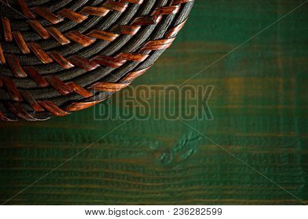Rattan Round Lid On Wooden Green Boards. Bright Green Wood Structure As A Background Texture Vignett