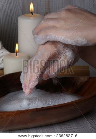 Female Hands, Covered With Soap Foam Next To The Burning Candles In The Office For Spa Procedures.