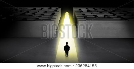 Businessman going straight ahead on a lighted carpet arrow between two maze
