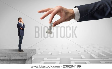 Little businessman from the top of the labyrinth fixing long term plan with big hand and chessman concept