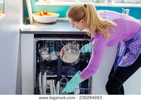Young Woman Putting Dirty Dishes To Dishwasher