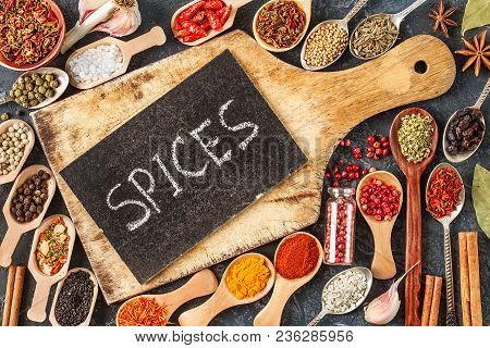 Indian Spices, Herbs And Empty  Cutting Board On Black Background.  Colorful Spices, Top View. Organ