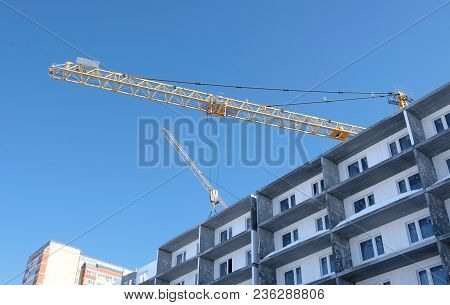 Construction Of A Multi-storey Building. Construction Crane. Unfinished Multi-storey House With Wind