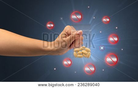 Hand giving pills with anti-drug concept and not allowed signs around