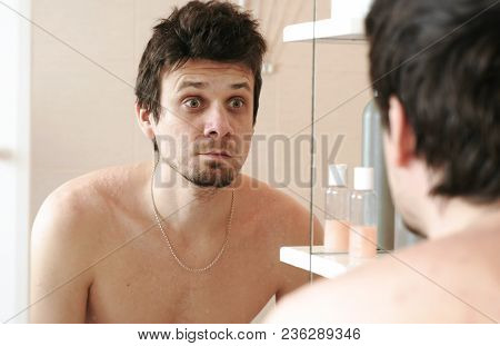 Tired Man Who Has Just Woken Up Looks At His Reflection In The Mirror And Surprised