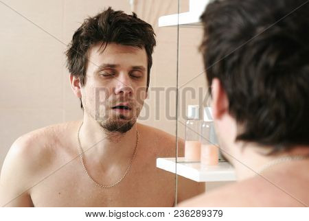 Tired Man Who Has Just Woken Up Looks At Its Reflection In The Mirror And Sleeping Standing Still.