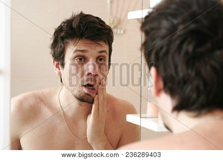 Tired Man Who Has Just Woken Up Looks At His Reflection In The Mirror Slaps His Cheek With His Hand