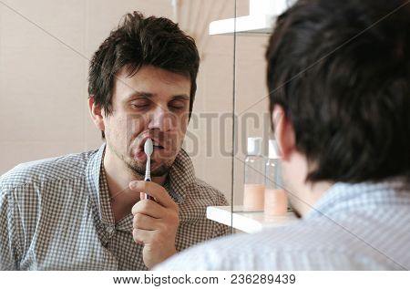 Tired Sleepy Man With A Hangover Who Has Just Woken Up Brush His Teeth, Looks At His Reflection In T