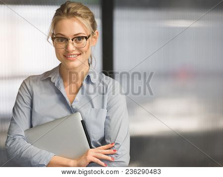 Waist Up Portrait Of Confident Blond Woman Holding Laptop And Smiling. She Is Standing Formalwear An