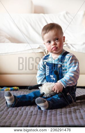 Portrait Of Cute Baby Boy With Down Syndrome Playing In Home Living Room