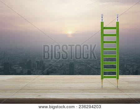 Green Pencil Ladder On Wooden Table Over Aerial View Of Cityscape At Sunset, Vintage Style, Business
