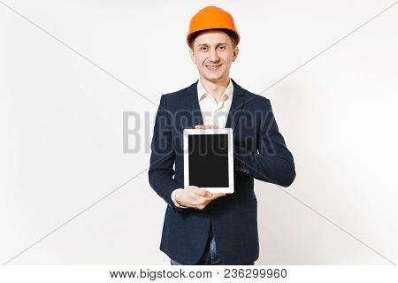 Young Handsome Smiling Businessman In Dark Suit, Protective Hardhat Holding Tablet Pc Computer With