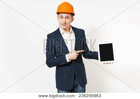 Young Handsome Businessman In Dark Suit, Protective Hardhat Pointing Index Finger On Tablet Pc Compu