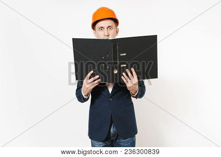 Young Concerned Businessman In Dark Suit, Protective Hardhat Holding Black Folder For Papers Documen