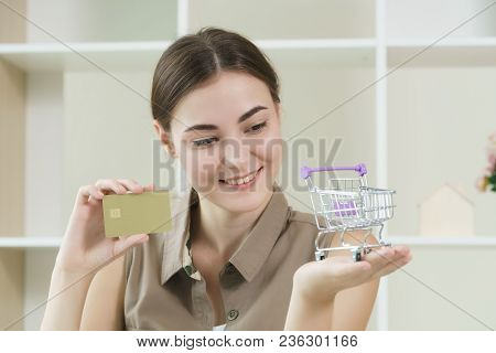 Woman Showing Credit Card And Shopping Cart.