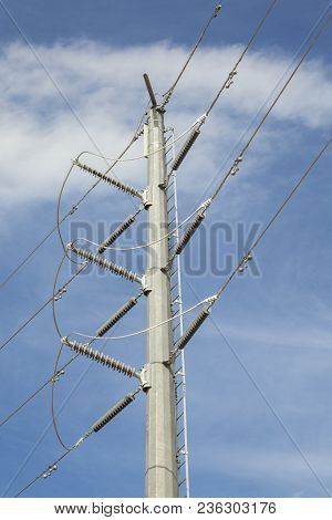 Many High Voltage Power Lines On A Single Mast On A Blue Sky Background