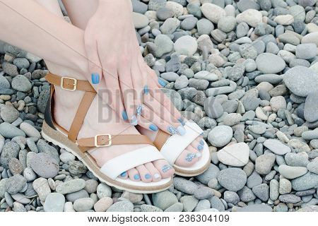 Female Feet In Sandals And Hands With A Blue Manicure On Pebbles. Top View