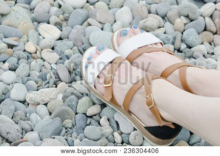 Female Feet In Sandals, Pebbles, Close Up