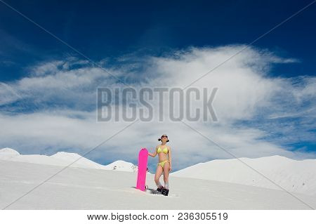 Sexy Snowboarder Woman Dressed In A Swimsuit Standing On A Mountain Top With A Pink Board