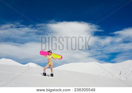 Slim Sexy Girl Dressed In A Bright Yellow Swimsuit With A Snowboard On The Shoulders