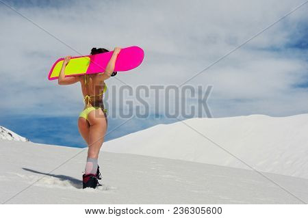 Back View Of Slim Sexy Girl Dressed In A Bright Yellow Swimsuit With A Snowboard On The Shoulders