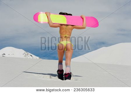 Back View Of Sexy Girl Dressed In A Bright Yellow Swimsuit With A Snowboard On The Shoulders