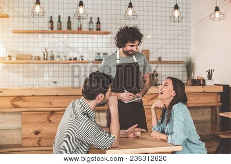 You Choose. Joyful Girl Ordering Food In Cafeteria And Laughing While Her Boyfriend Is Pointing Fing