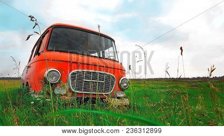 Russia, St. Petersburg, 21.07.2017 - Red Car In The Grass On The Field. The Car 60-ies.