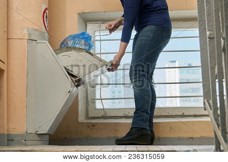 Woman Throwing Away A Garbage Packed In A Garbage Bag Using A Home Garbage Chute In Moscow Dwelling